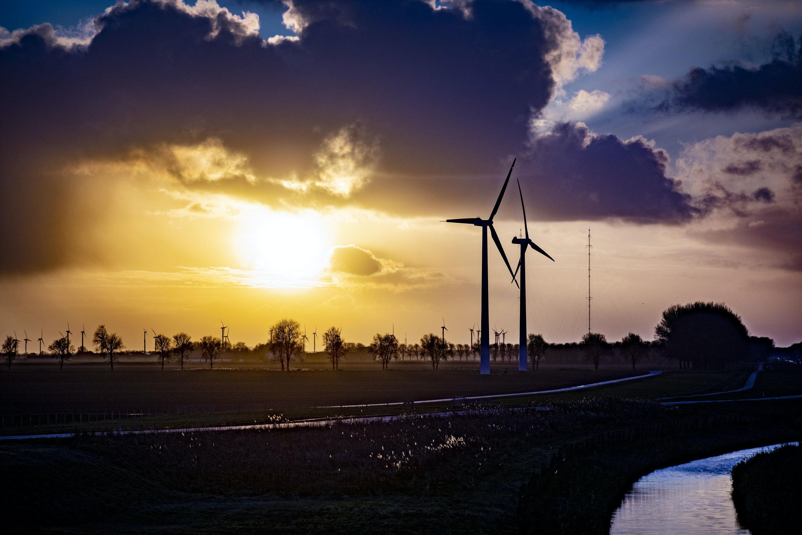 Windturbines bij een ondergaande zon. Foto Rob Voss