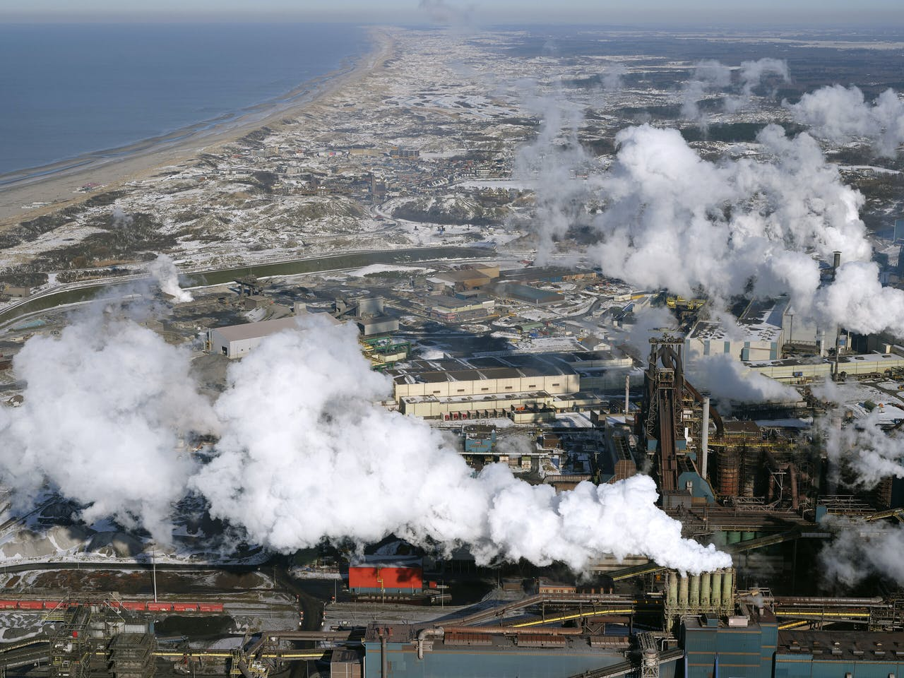 Luchtopname van het terrein van Tata Steel. Sluiten van 'IJmuiden' zou Nederland in één klap veel CO2-uitstoot besparen, evenals overlast voor omwonenden, kopzorgen voor toezichthouders en miljarden aan subsidies.