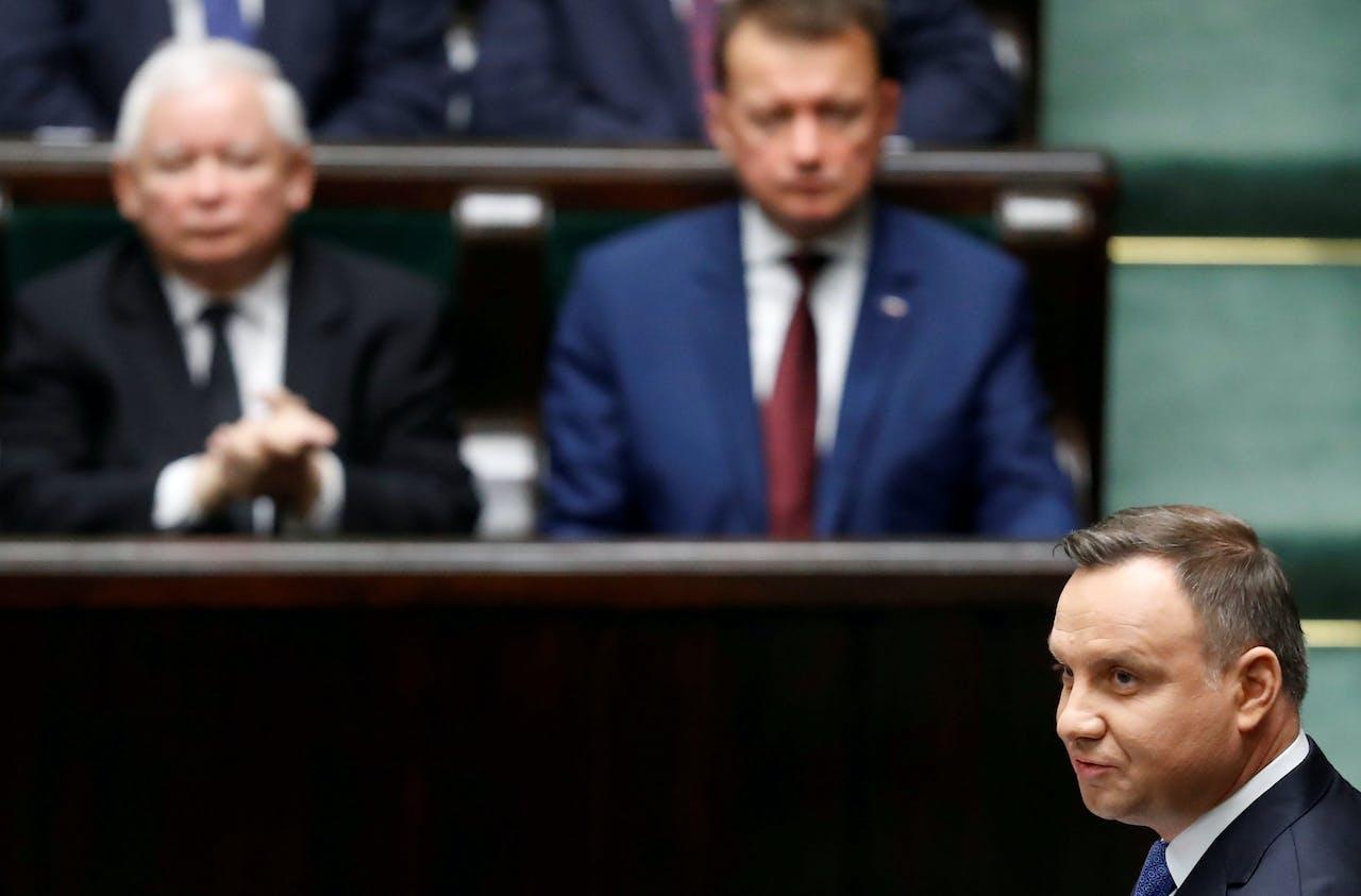 De Poolse president Andrzej Duda spreekt het parlement toe. Op de achtergrond links Jaroslaw Kaczynski, de leider van de regeringspartij PiS waaraan Duda is gelieerd.
