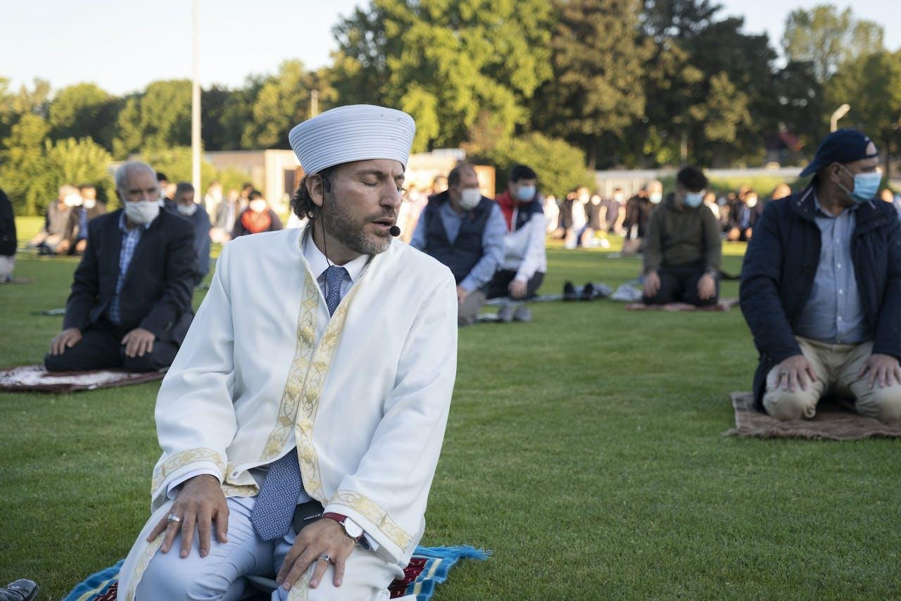 De preek van Irfan Turksever via de gloednieuwe geluidsinstallatie die de moskee speciaal voor het buitengebed heeft aangeschaft. De kleedjes liggen op anderhalve meter afstand van elkaar.