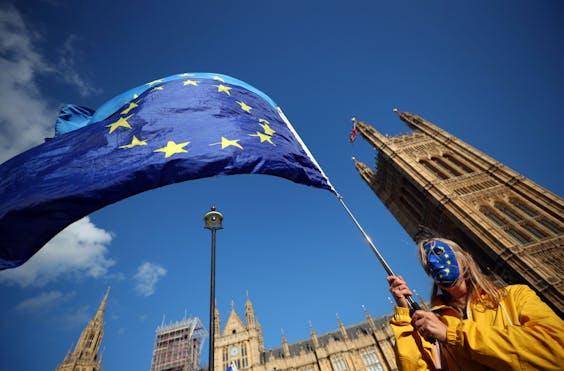 Een demonstrant zwaait met de Europese vlag voor het Britse parlementsgebouw in Londen.