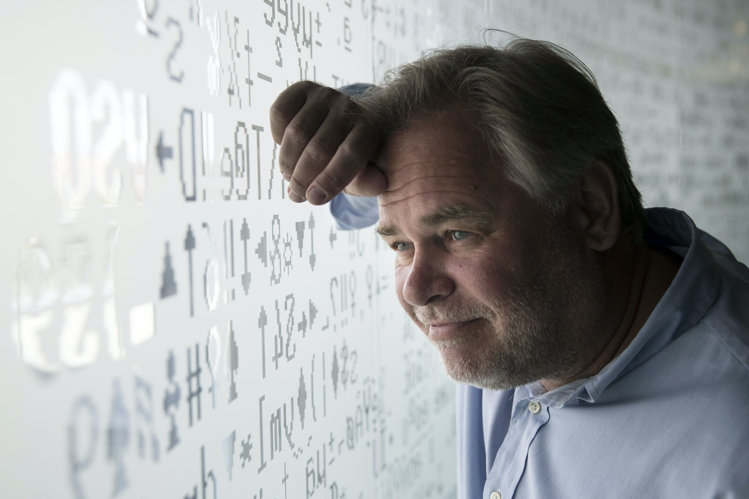 Eugene Kaspersky, Russian antivirus programs developer and chief executive of Russia's Kaspersky Lab, watches trough a window decorated with programming code's symbols at his company's headquarters in Moscow, Russia, Saturday, July 1, 2017. Kaspersky says he's ready to have his company's source code examined by U.S. government officials to help dispel long-lingering suspicions about his company's ties to the Kremlin. (AP Photo/Pavel Golovkin)