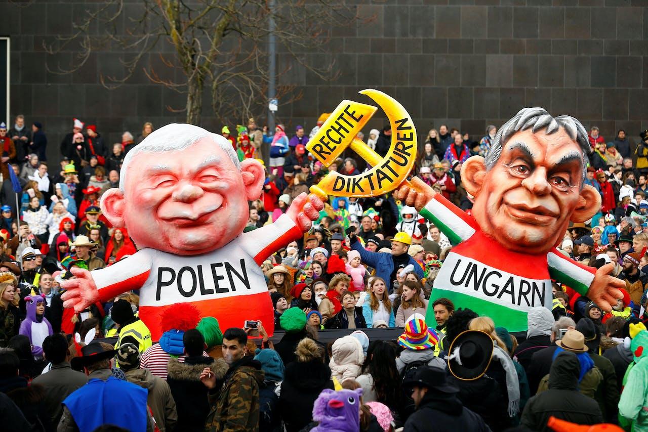 Carnavalsgangers lopen bij het carnaval van 2018 in Düsseldorf met poppen van Jaroslaw Kaczynski (l), de leider van de Poolse regeringspartij PiS, en de Hongaarse premier Viktor Orbán.