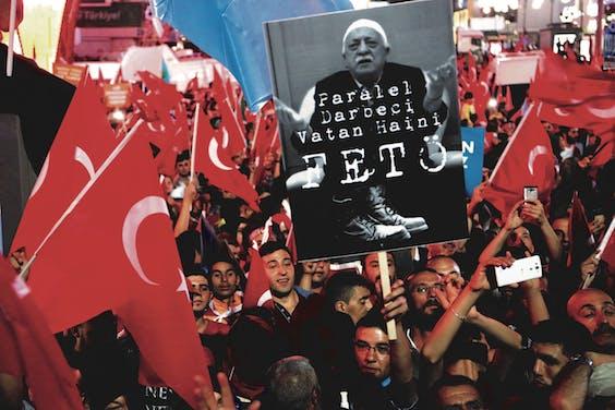 Demonstranten houden een bord omhoog met het portret van geestelijk leider Fethullah 'Feto' Gülen.