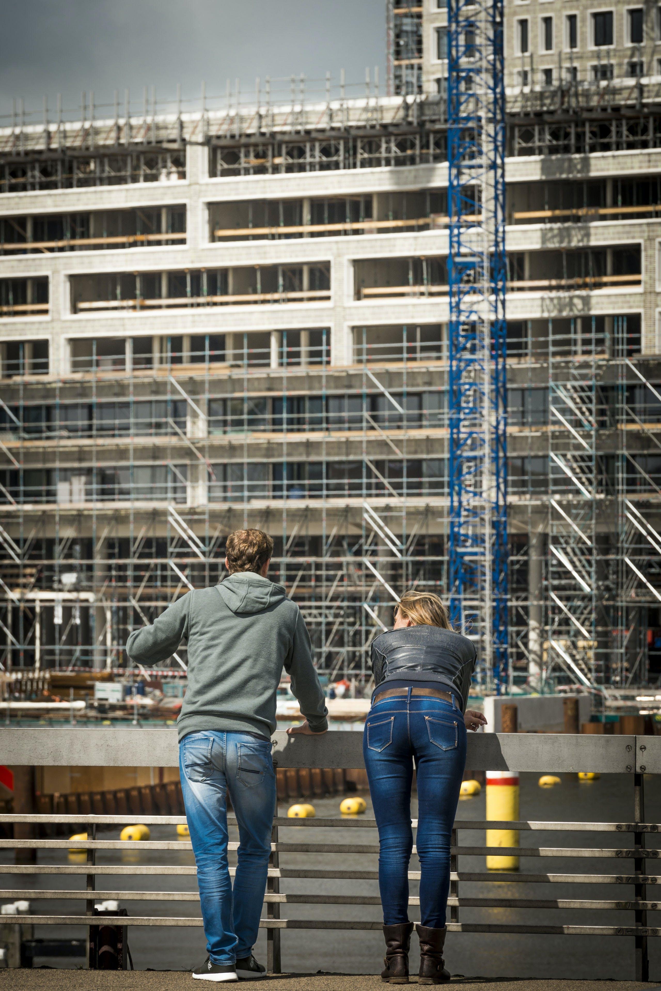 Een jong stel kijkt hoe het staat met de nieuwbouw in de Amsterdamse Houthavens.