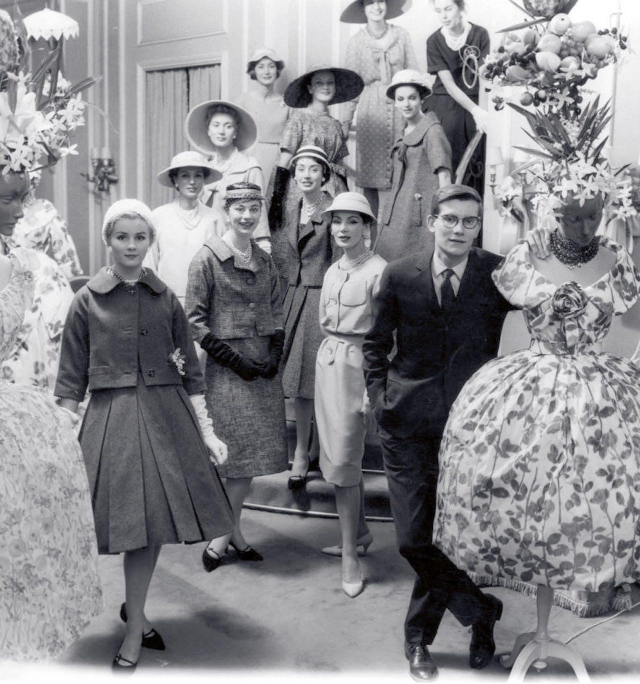 30 januari 1958. Saint Laurent met zijn modellen in de salon van Dior.