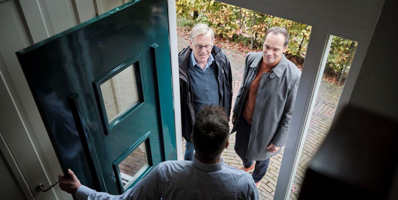 Frank Lentz en Maurits van Laarhoven op bezoek bij een van de bewoners van de Haagse wijk Ypenburg.