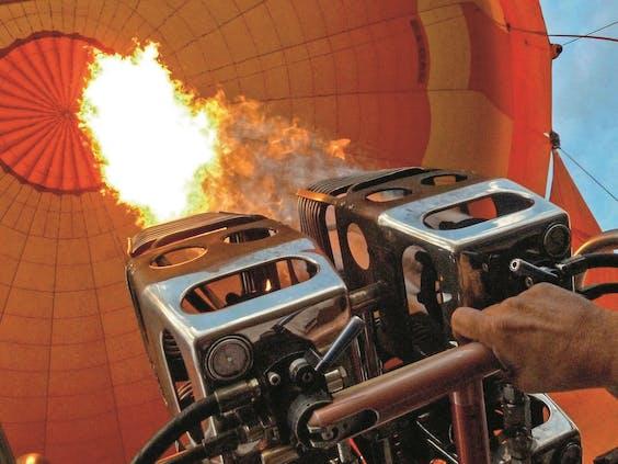 Met branders wordt met stootjes propaangas verbrand. Hete lucht vult de ballon.