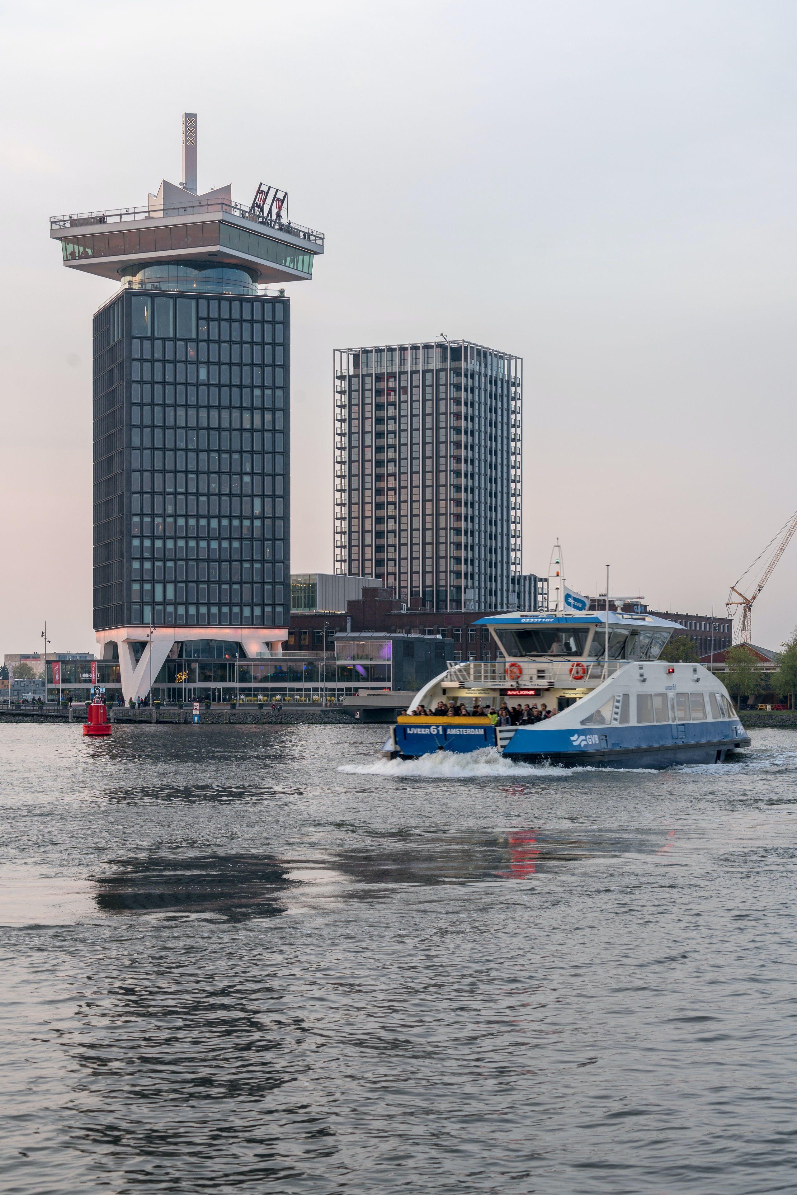 Links de nieuwe woontoren in Amsterdam-Noord, gezien vanaf de andere kant van het IJ.