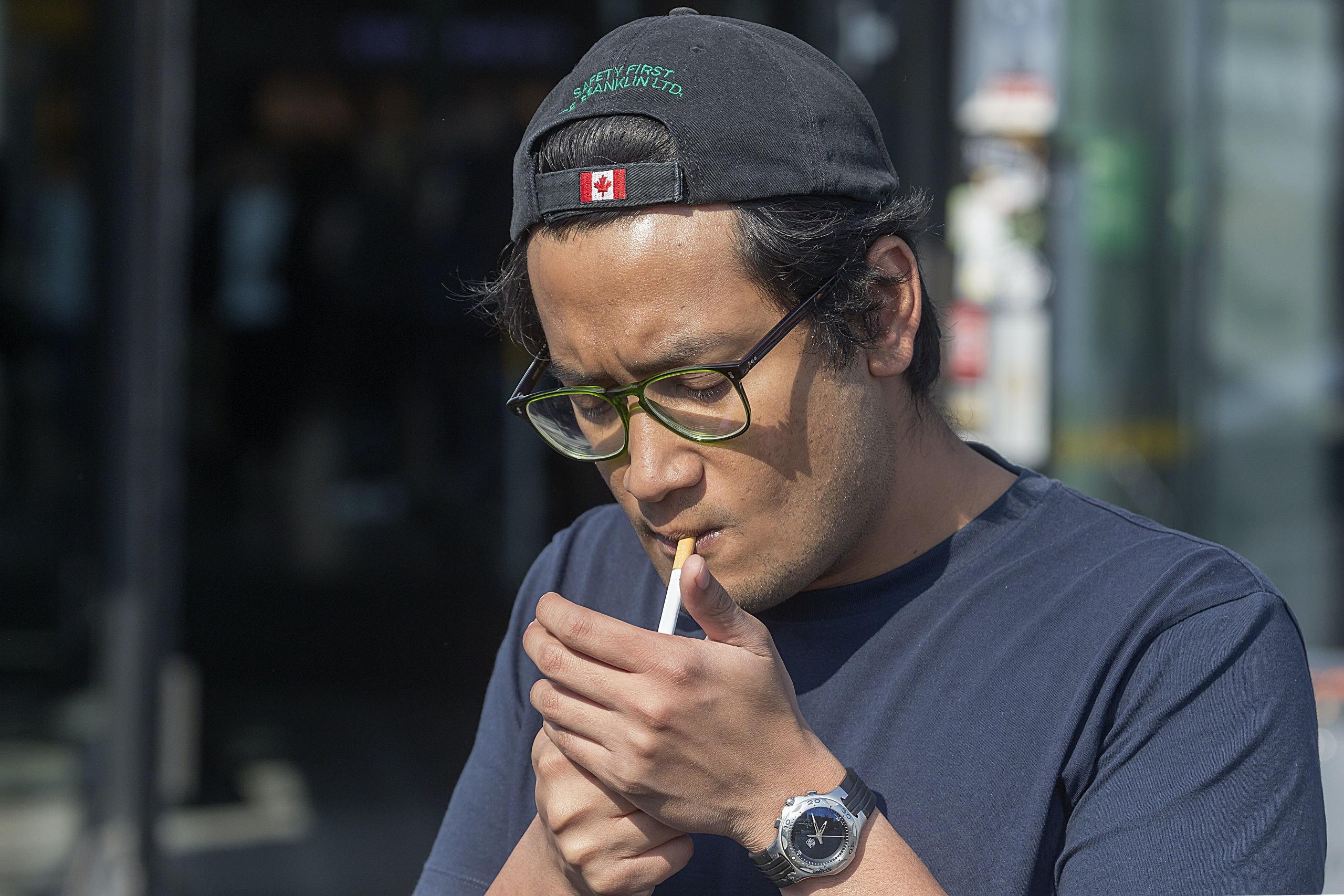 Foto: David Rozing Nederland Rotterdam 20 mei 2018 Schiphol Man rookt een sigaret tussen andere mensen. Meeroken, schadelijke effecten effect op de gezondheid. Smoking area rookzone.