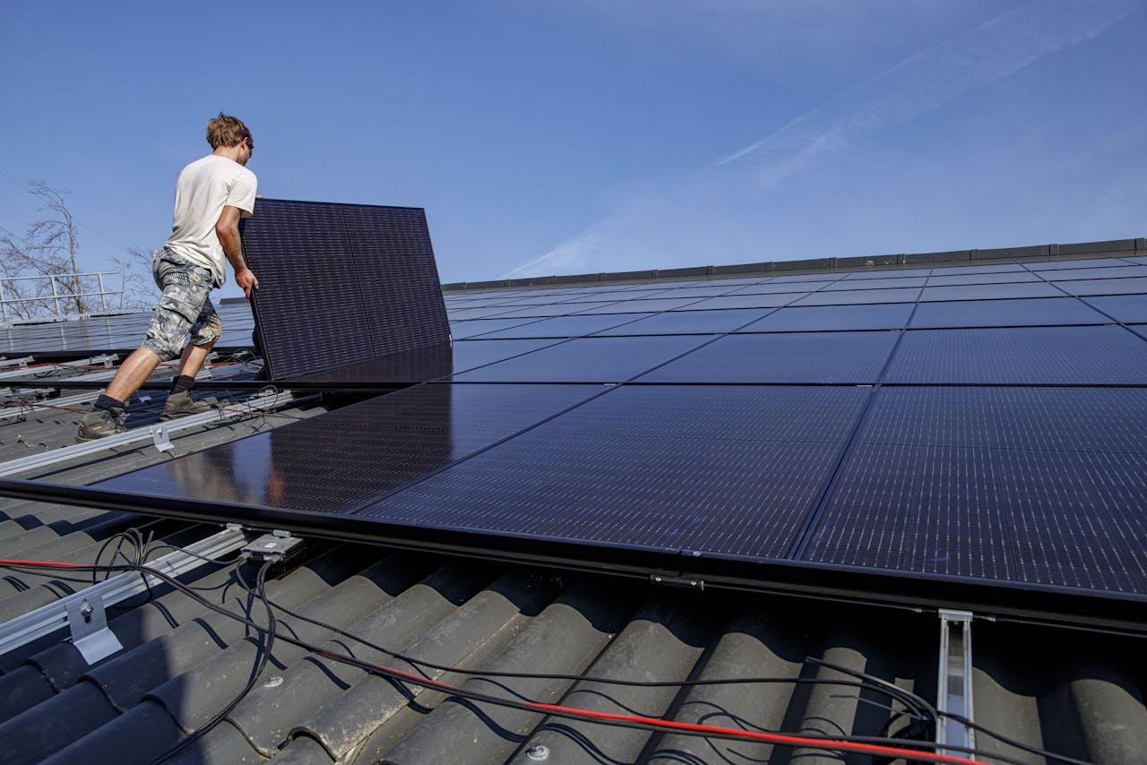 Op het dak van een stal van een boerderij worden zonnepanelen gelegd die stroom moeten opwekken. De meeste elektriciteit wordt terug gegeven aan het elektriciteitsnet.