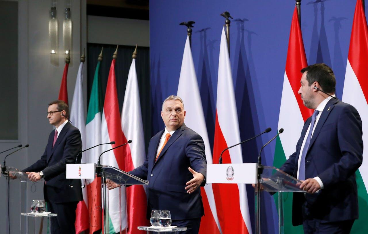 Van links naar rechts: de Poolse premier Morawiecki, zijn Hongaarse collega Orbán en Matteo Salvini (ondanks de presentatie op het podium geen premier maar leider van de rechts-nationalistische Lega in Italië).
