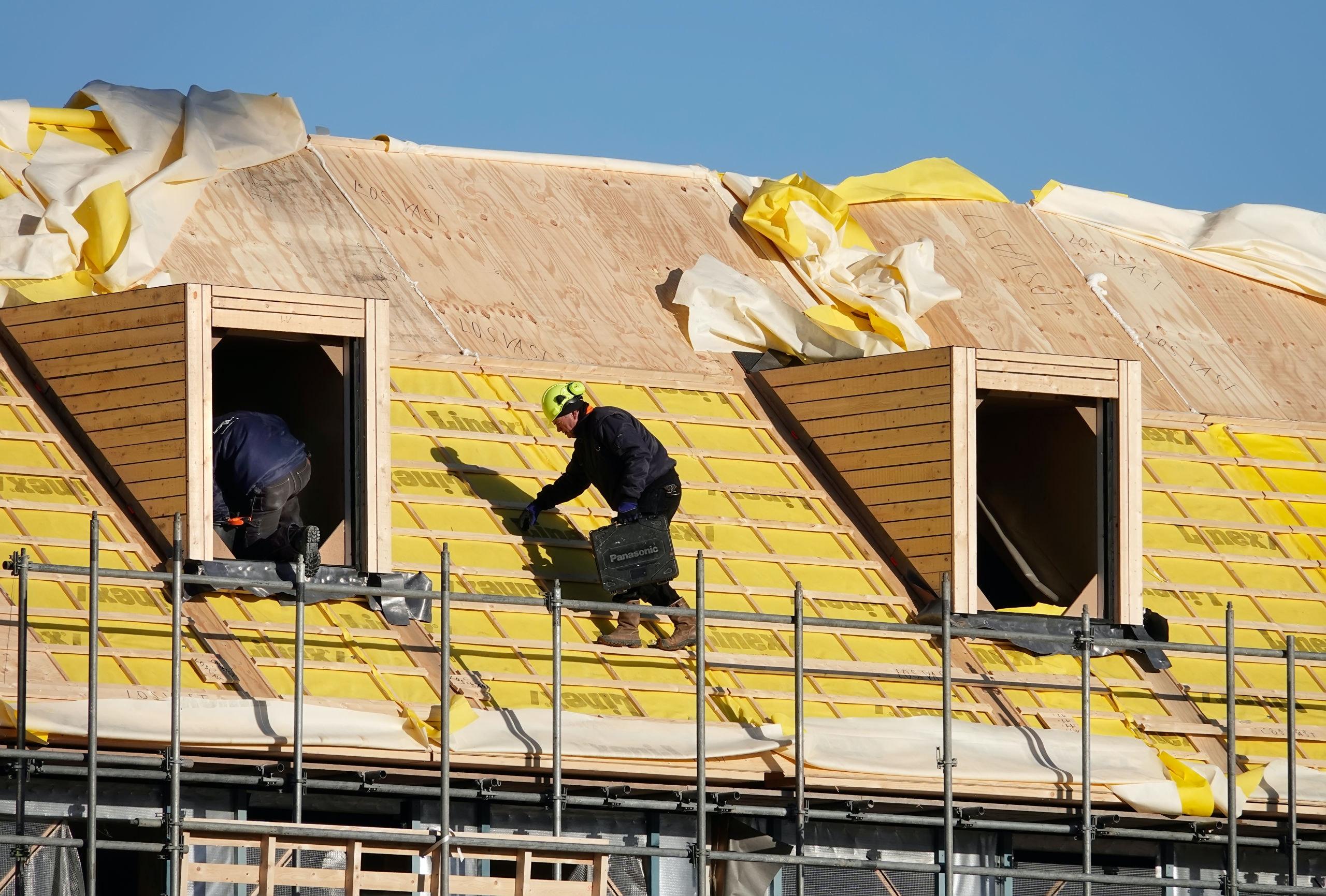 Nederland -  Amsterdam -  2018.  Nieuwbouw bij de Houthavens. Bouwvakkers op een dak. Foto Berlinda van Dam / Hollandse Hoogte. Foto Berlinda van Dam / Hollandse Hoogte
