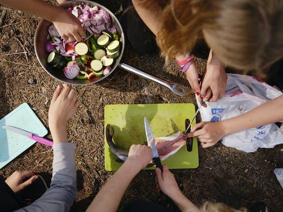 Tijdens de 'bivak' helpen de kinderen met koken. Op het menu staat zelf gevangen forel.