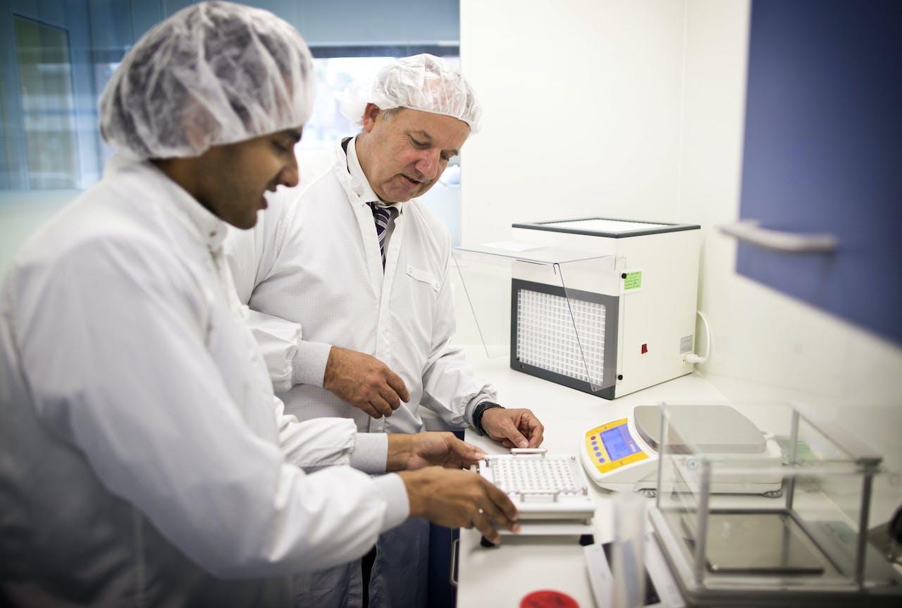 Lebbink en assistent (links) behoort met zijn Transvaal Apotheek inmiddels tot de minderheid van apothekers die nog in staat is zelf medicijnen te bereiden.