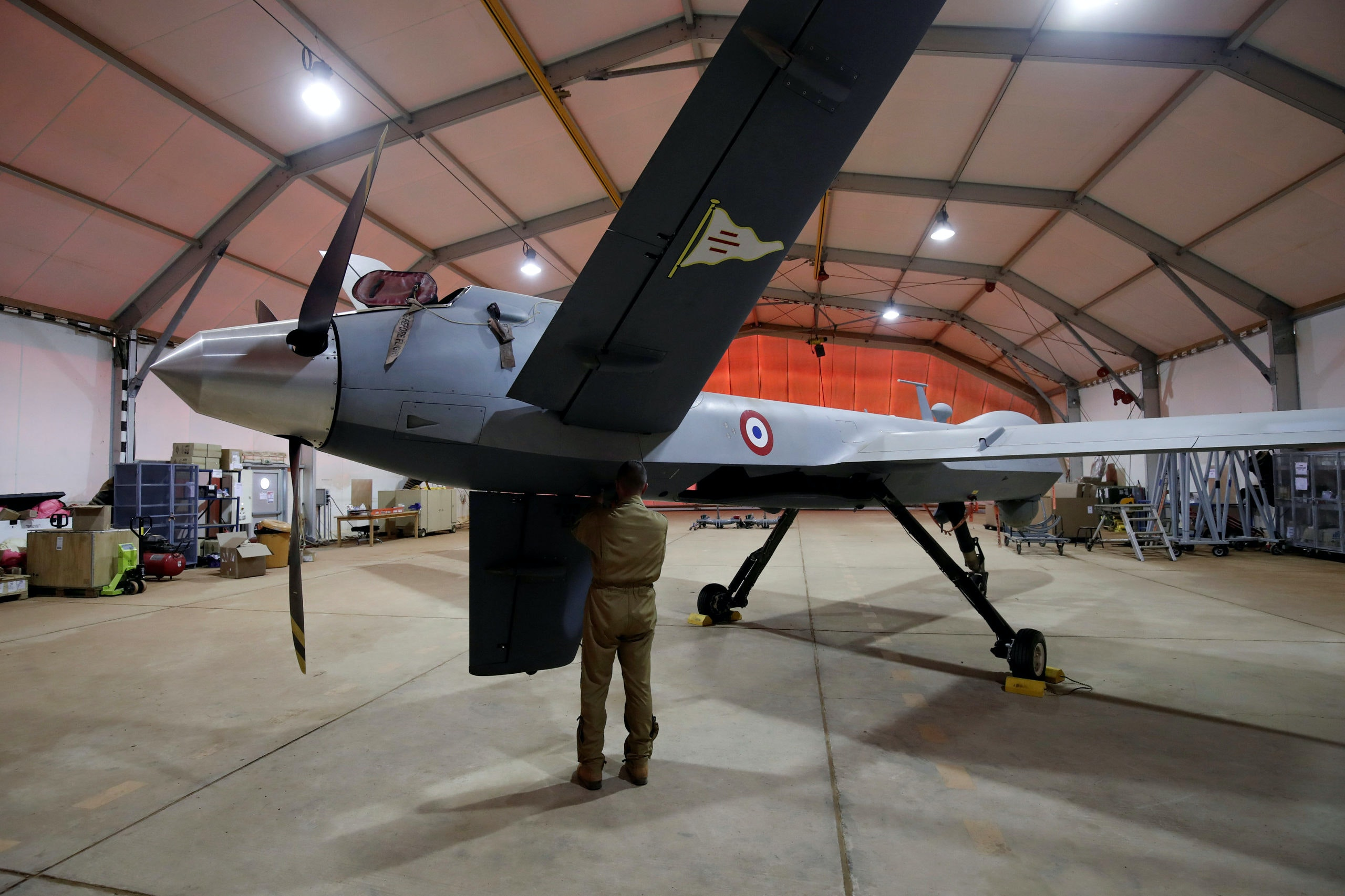 A French soldier of the regional anti-insurgent Operation Barkhane stands in front of a General Atomics MQ-9 Reaper drone version Block 1 in Niamey, Niger, October 21, 2017. REUTERS/Benoit Tessier