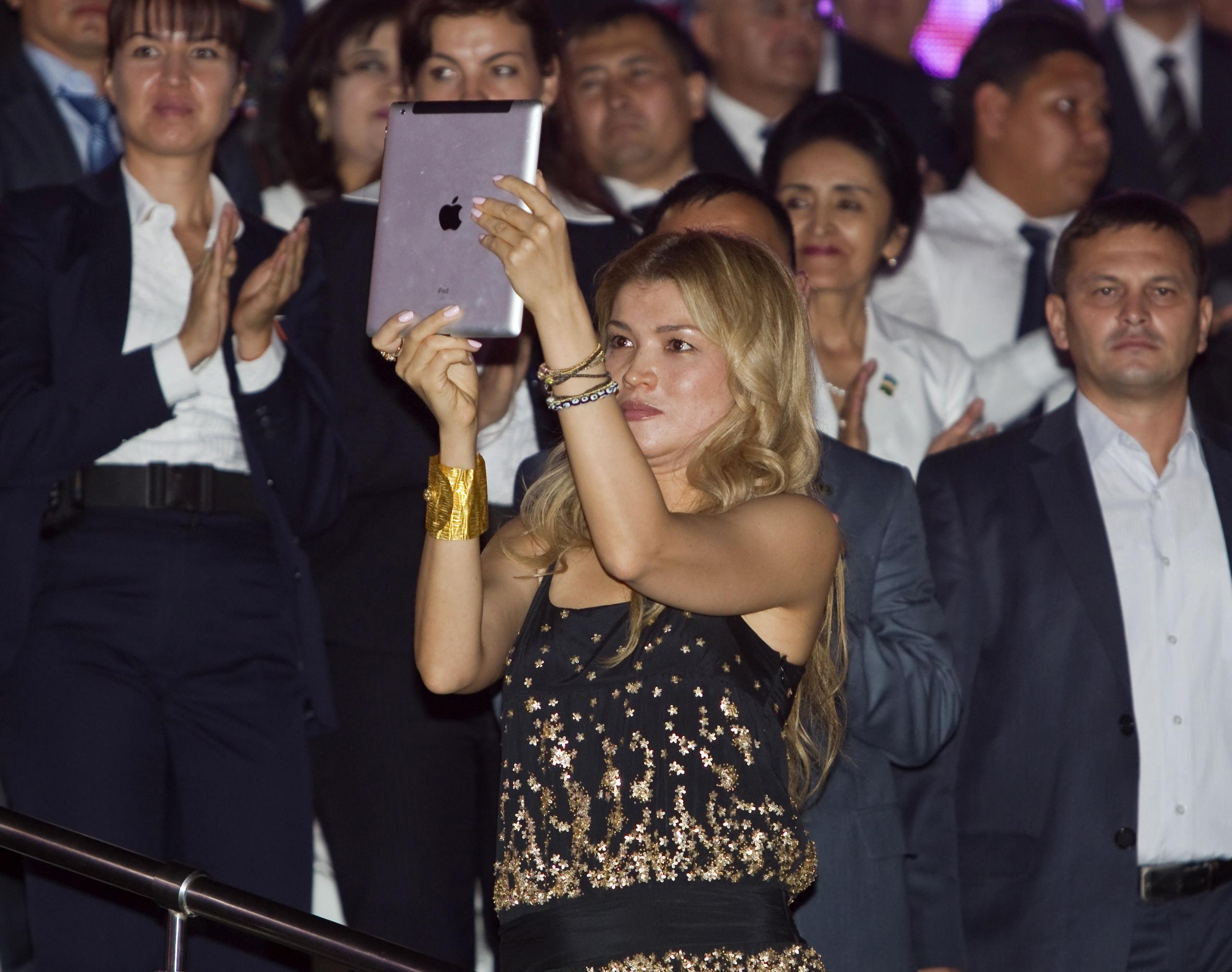 Gulnara Karimova (C), daughter of Uzbekistan's President Islam Karimov, takes a video with an Ipad as her father dances during an Independence Day celebration in Tashkent August 31, 2012. Uzbekistan is marking the 21st anniversary of independence.  REUTERS/Shamil Zhumatov  (UZBEKISTAN - Tags: POLITICS ANNIVERSARY) - GM1E8910FYR01