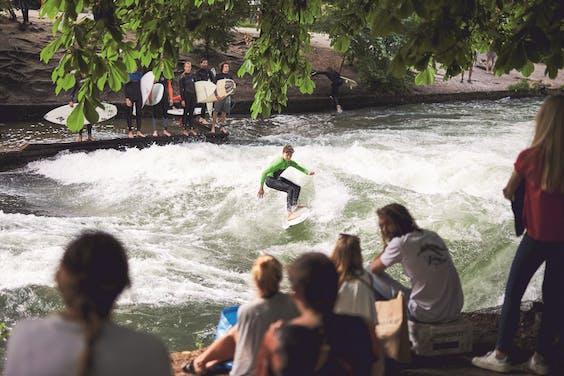 Surfers trekken de aandacht op de golven van de Eisbach, in de Englischer Garten.