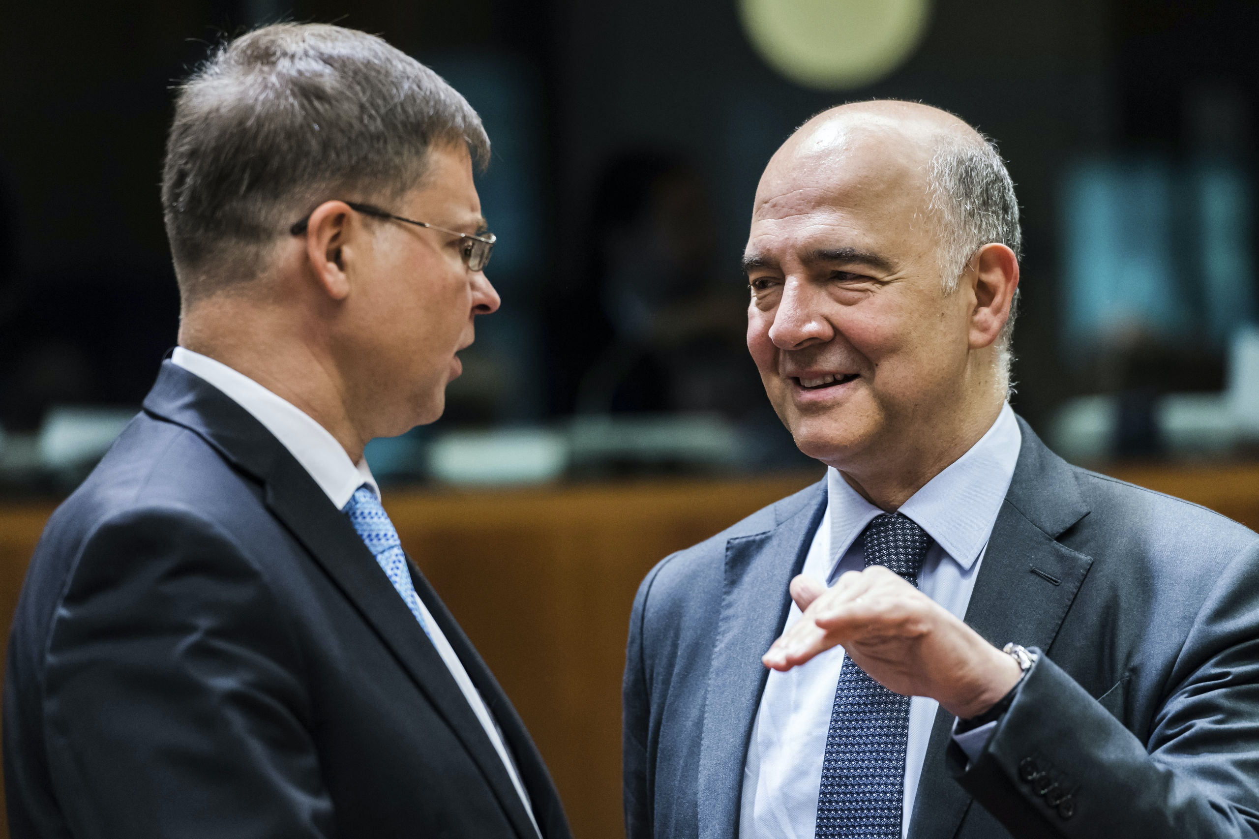 EU Commission Vice-President Valdis Dombrovskis, left, talks with EU Commissioner for Economic and Financial Affairs, Taxation and Customs Pierre Moscovici prior to a meeting of EU finance ministers at the EU Council building in Brussels, Tuesday July 11, 2017. (AP Photo/Geert Vanden Wijngaert)