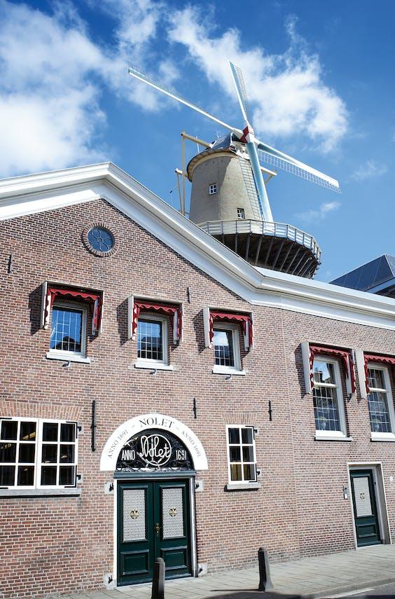 De ingang van de distilleerderij aan de Hoofdstraat, met molen De Nolet op de achtergrond.