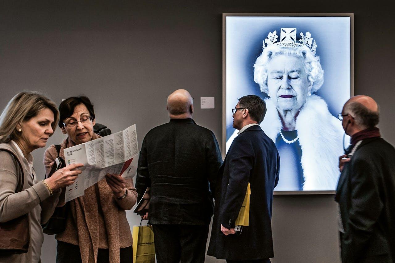 Bezoekers van de Tefaf bij een portret van Queen Elisabeth II door de Canadese Chris Levine, genaamd 'Lightness of Being' (foto: Hollandse Hoogte).