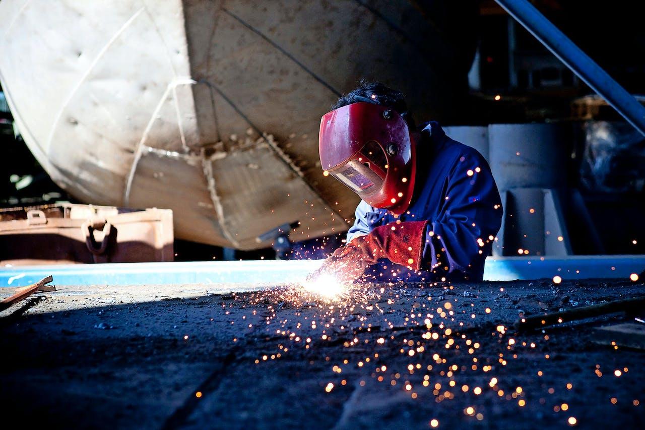 Metaalbewerker verricht laswerkzaamheden in de metaal-industrie, scheepsbouw.