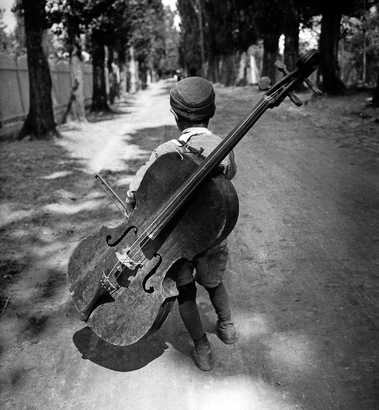 Hongarije, Balatonmeer, 1931. Zigeunerjongen met een cello op zijn rug, Eva Besnyö. Formaat: 40 x 43,3 cm.