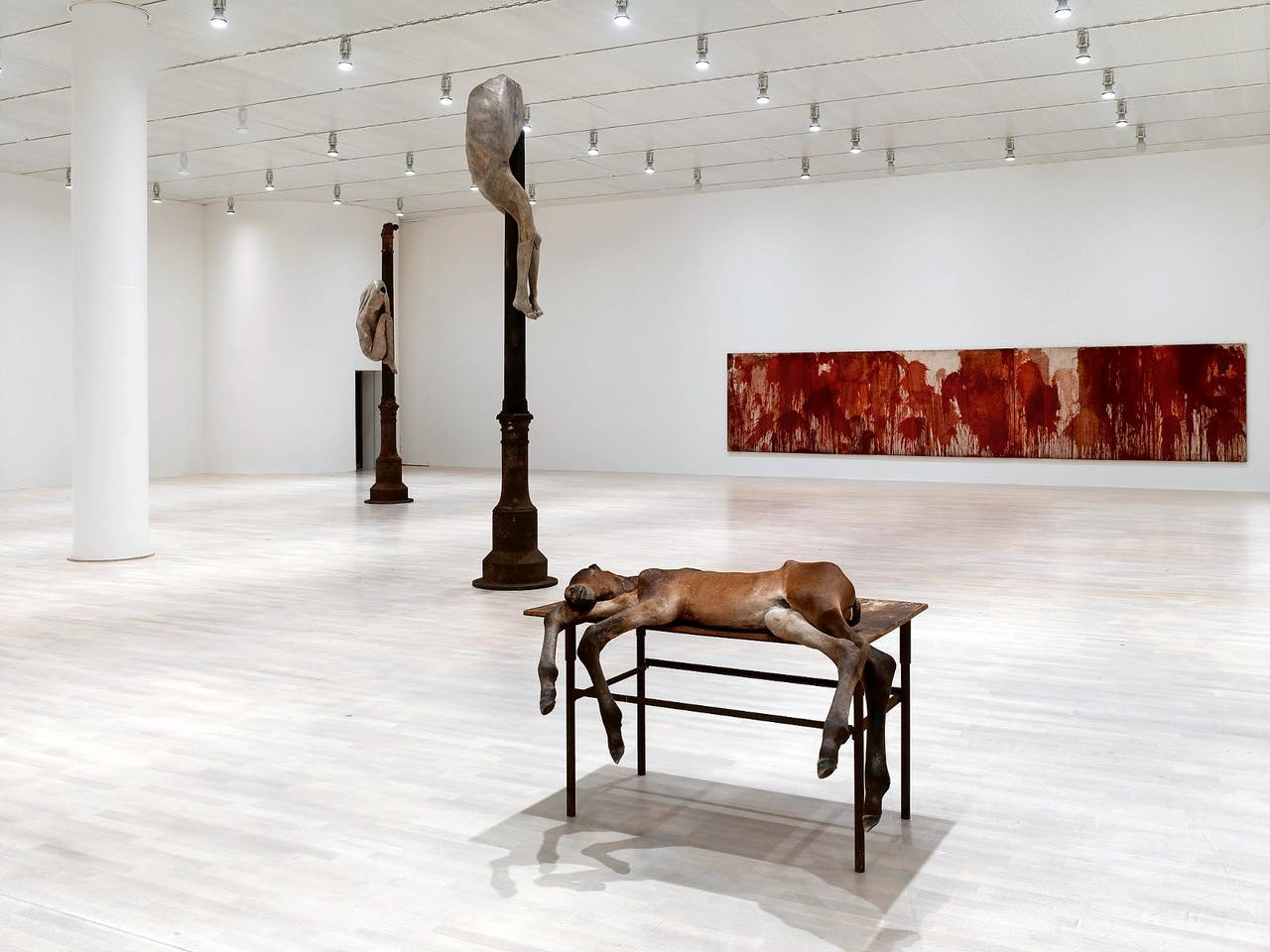 Links: Berlinde De Bruyckeres 'Schmerzenmannen' (2005) en op de voorgrond 'Lost III' (2011), ook van haar hand. Aan de wand 'Passionsfries' van de Duitser Hermann Nitsch, uit 1962.