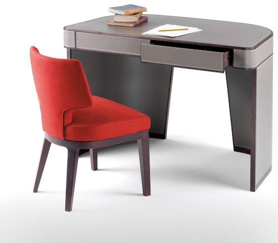 Bureau Amos, gemaakt van met leer overtrokken hout. Erbij: stoel Aline.