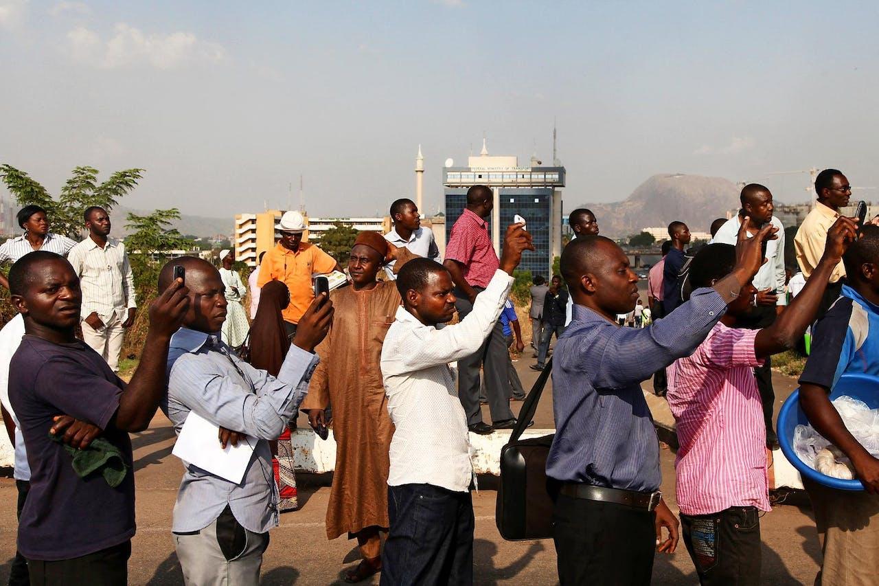 Omstanders in de Nigeriaanse stad Abuja maken foto's van een brandende olieterminal. (HH)