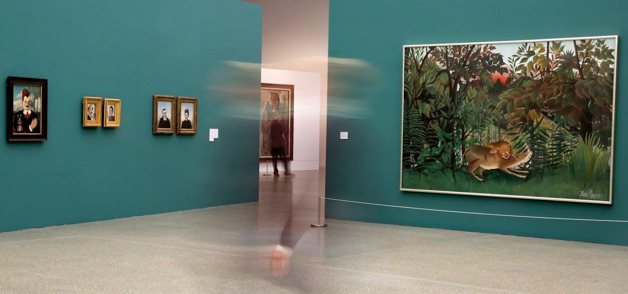 Overzicht van expositie in Essen. Rechts: 'De hongerige leeuw stort zich op de antilope' (1905) van Henri Rousseau, een beroemde autodidact. Geheel links zijn portret van 'Monsieur X' (1905-1906).