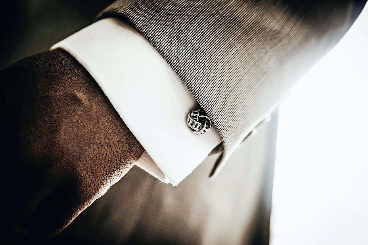 De simpelste manchetknoop is een zijden knoopje, een zilveren uitvoering kan ook.