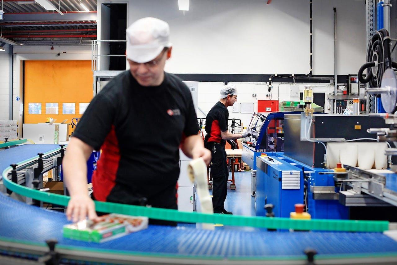 Twee arbeidsgehandicapten aan het werk bij folieproducent ITS in Apeldoorn. Het bedrijf heeft vijf werkplekken voor mensen met een arbeidshandicap. Foto's: Marijn Alders voor het FD