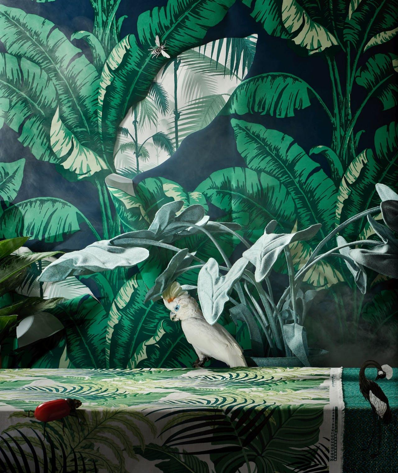 Behang op achtergrond 'La Havane', € 166 p/rol, Nobilis via Wilhelmine van Aerssen; behanguitsnede in palmblad 'Palm Jungle', €124, Cole and Son via Luxury By Nature; plant aglaonema silver bay, mooiwatplantendoen.nl; rode kever, €20, Zara Home; interieurstof 'Manila', €78, Sanderson via Luxury by Nature; kaketoe, €745, Luxury by Nature; vilten plant alocasia in Divina Kvadrat-stof, €1175, Wandschappen; groene stof 'Vanuatu', €99, Pierre Frey via Luxury by Nature.