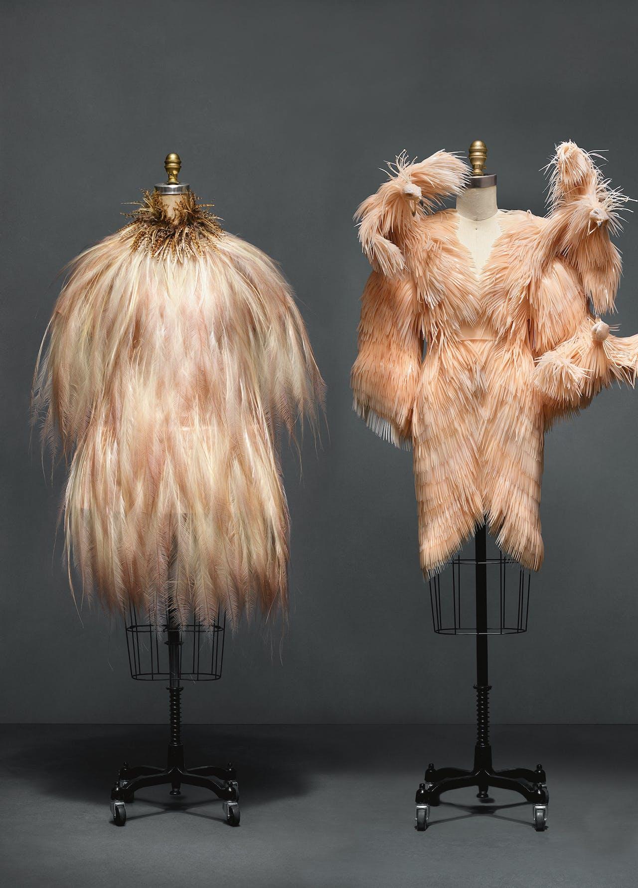 Handgemaakte haute couture-jurk uit 1969 van Yves Saint Laurent van zijde en veren (l) en deels 3D-geprint ontwerp van siliconen en katoen van Iris van Herpen uit 2013.