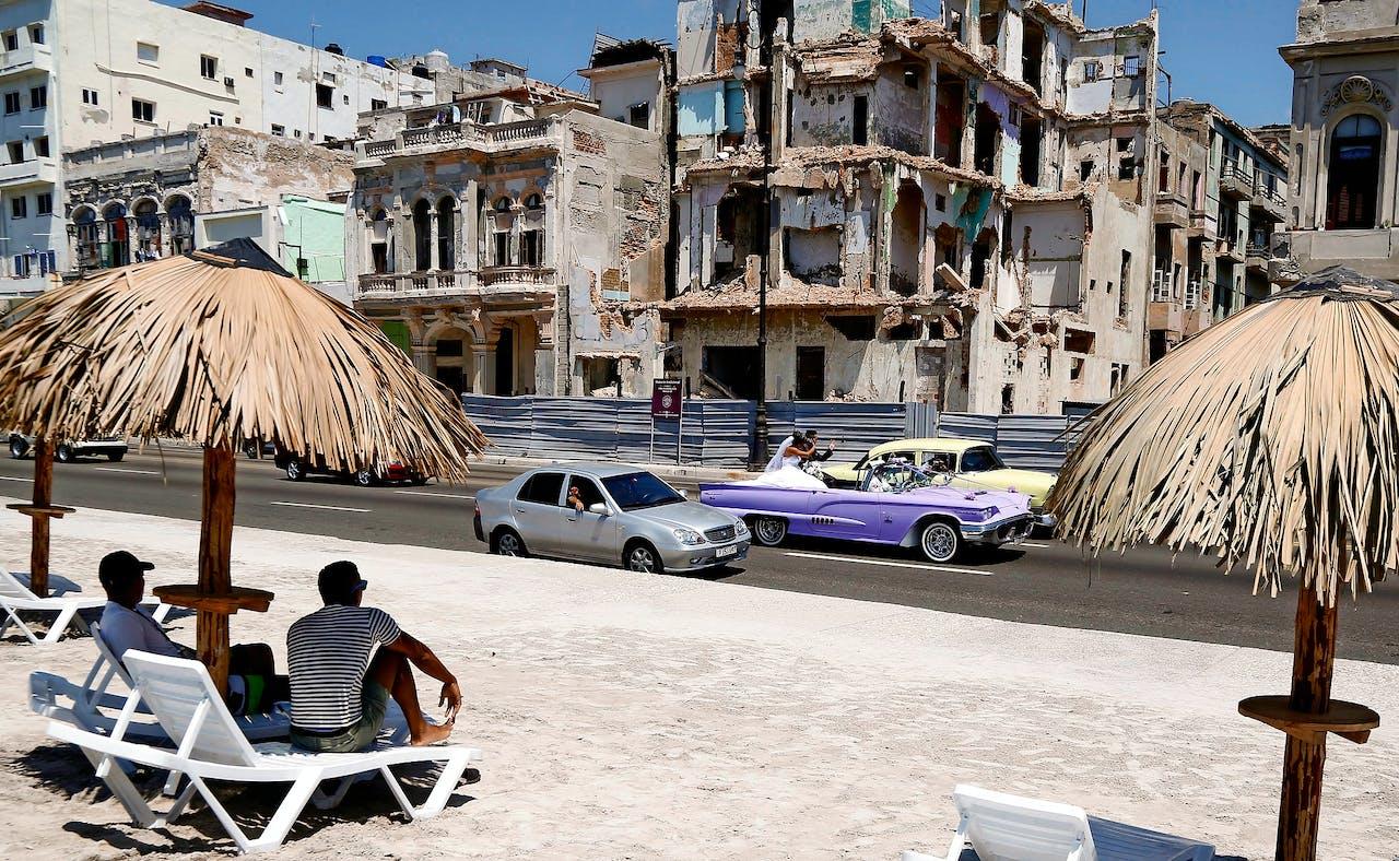 Maken deze vervallen panden eerdaags plaats voor flitsende hotels? Zullen oldtimers straks wijken voor moderne auto's? (AP Photo/Desmond Boylan)