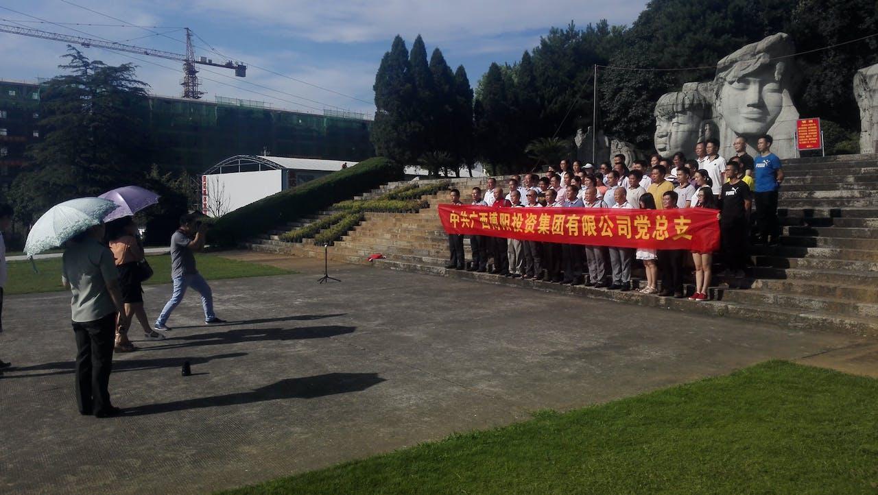 Medewerkers van investeringsmaatschappij Guangxi Bu Yang poseren voor een foto in het herdenkingspark van de veldslag bij de Xiangrivier. Op de achtergrond verschillende sculpturen, die volgens de samenstellers van het park de 'heroïsche veldslag' moeten representeren (Foto: Sjoerd den Daas)