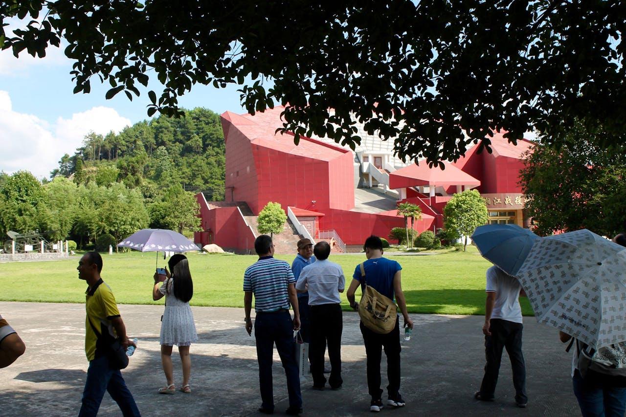 """Op de voorgrond enkele bezoekers van het Herdenkingspark. Op de achtergrond de herinneringshal van de veldslag bij de Xiangrivier. Het hoofdgebouw is ontworpen naar de stijl van de hoeden van het Rode Leger droegen, """"een rode ster onder de rook van buskruit"""", aldus een van de medewerkers van de hal. (Foto: Sjoerd den Daas)"""