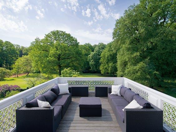Het grote balkon van het landhuis biedt nu plaats aan loungebanken.