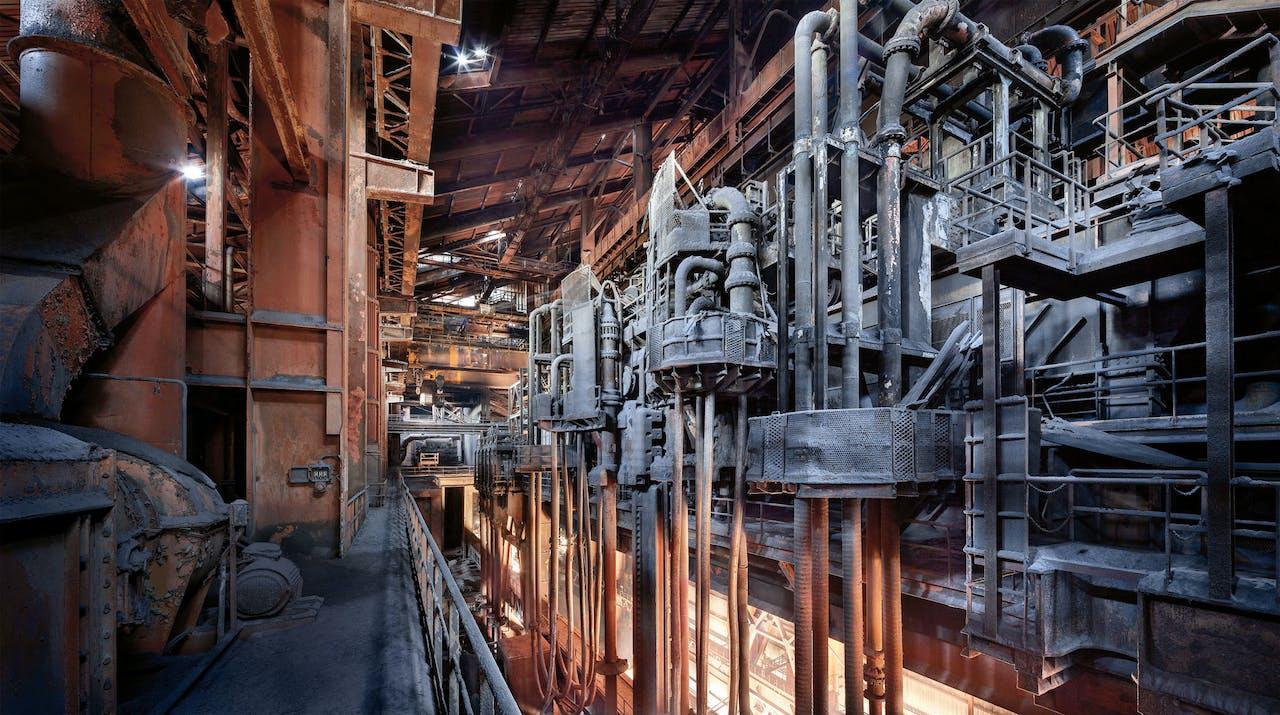 'Staalgigant', 2011-12. Verlaten staalfabriek in Frankrijk. Het oktoberlicht laat het staal van de hoogoven voor een laatste maal gloeien. Jan Stel vroeg geen toestemming om er te fotograferen. Dan zou hij nooit zo hoog hebben mogen klimmen.
