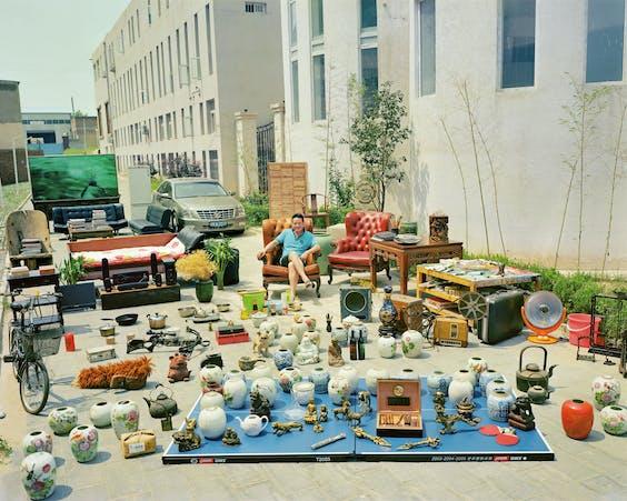 Foto van Huang Qingjun uit zijn serie 'Family Stuff'. Hier is de 40-jarige kunstenaar Wenjue He vastgelegd bij zijn huis in Peking.