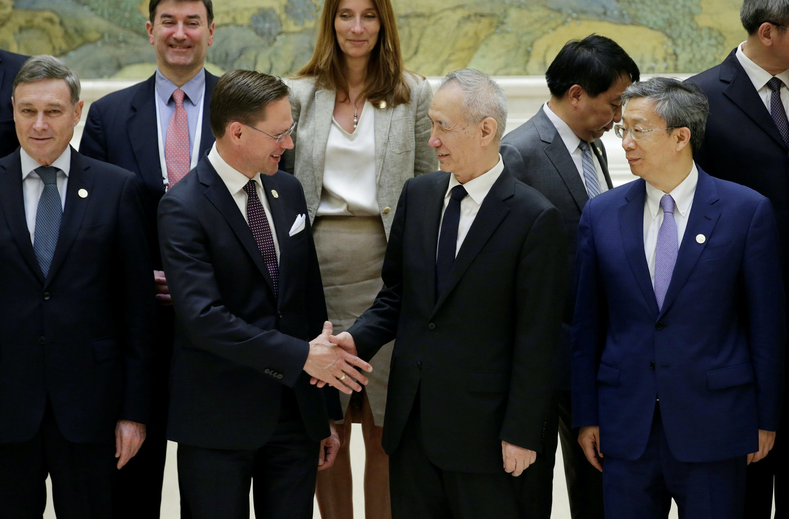 European Commission Vice President Jyrki Katainen shakes hands with Chinese Vice Premier Liu He, next to China's central bank governor Yi Gang after a group photo event during the EU-China High-level Economic Dialogue at Diaoyutai State Guesthouse in Beijing, China June 25, 2018. REUTERS/Jason Lee
