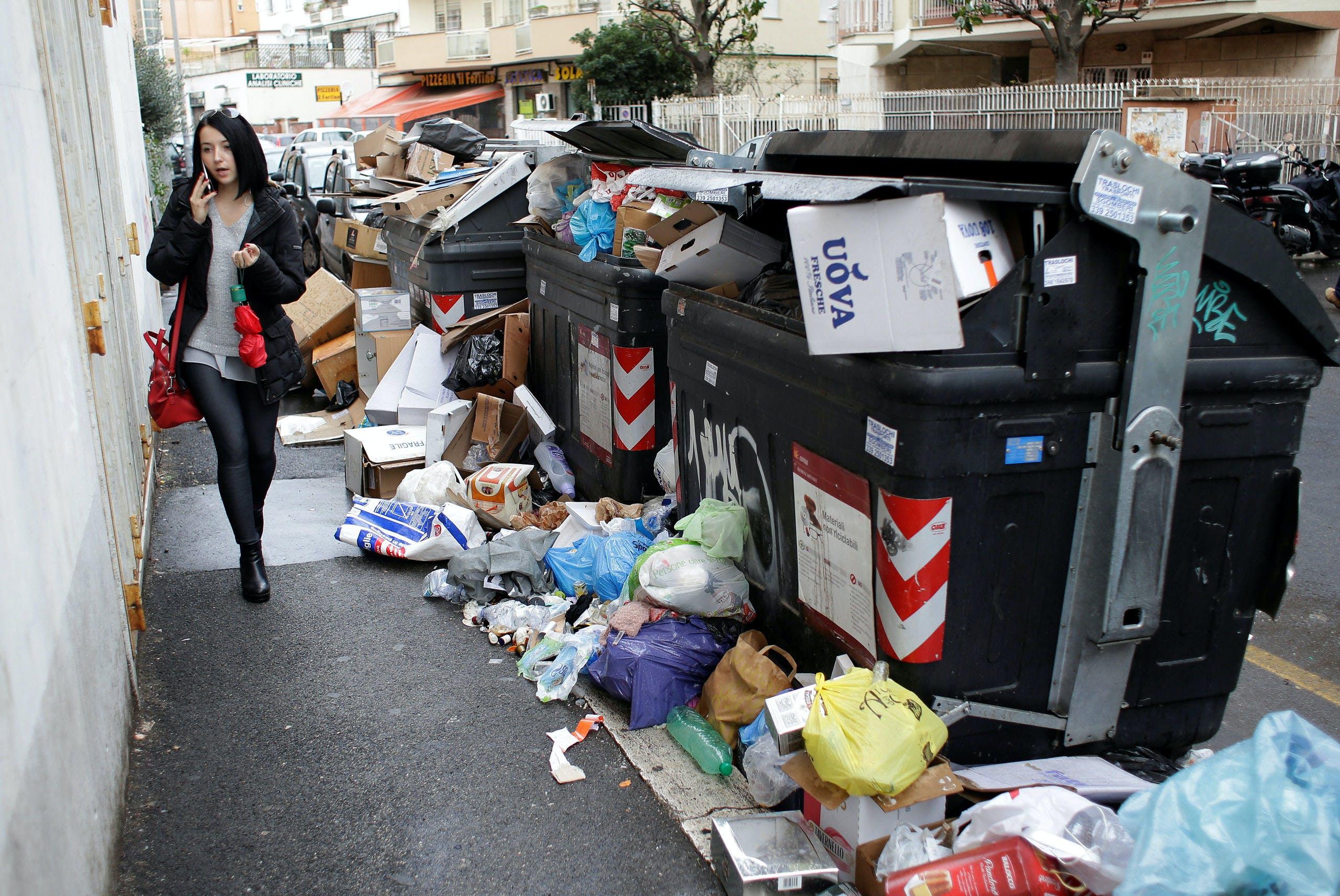 Een Romeinse vrouw loopt langs een berg afval. Noordelijke eurolanden willen dat Italië de risico's op bankbalansen helpt verminderen voordat ze een gezamenlijke Europese schuld willen uitgeven.