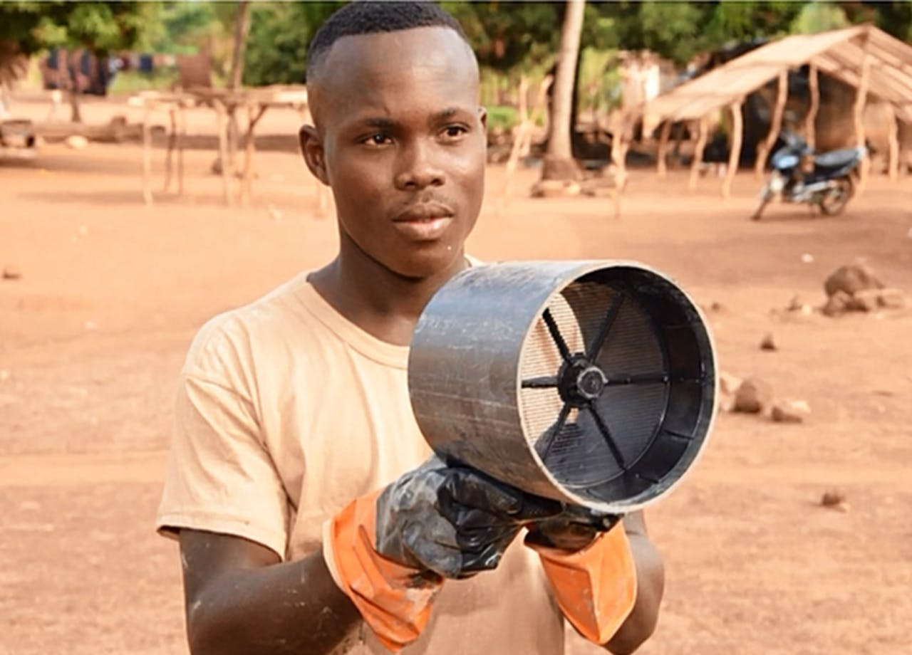 Een man in Ivoorkust demonstreert de ventilatiebuis van Anne Osinga. Muggen vliegen erin omdat ze de geur van mensen ruiken, maar gaan snel dood omdat er roosters met gif in de buis zitten.