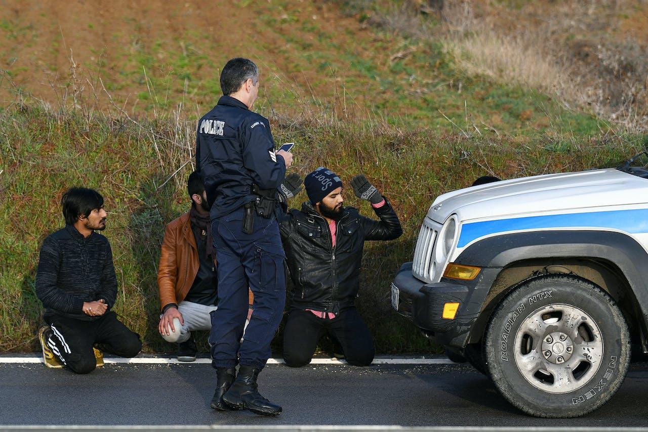 Een Griekse agent houdt de wacht bij Pakistaanse migranten.