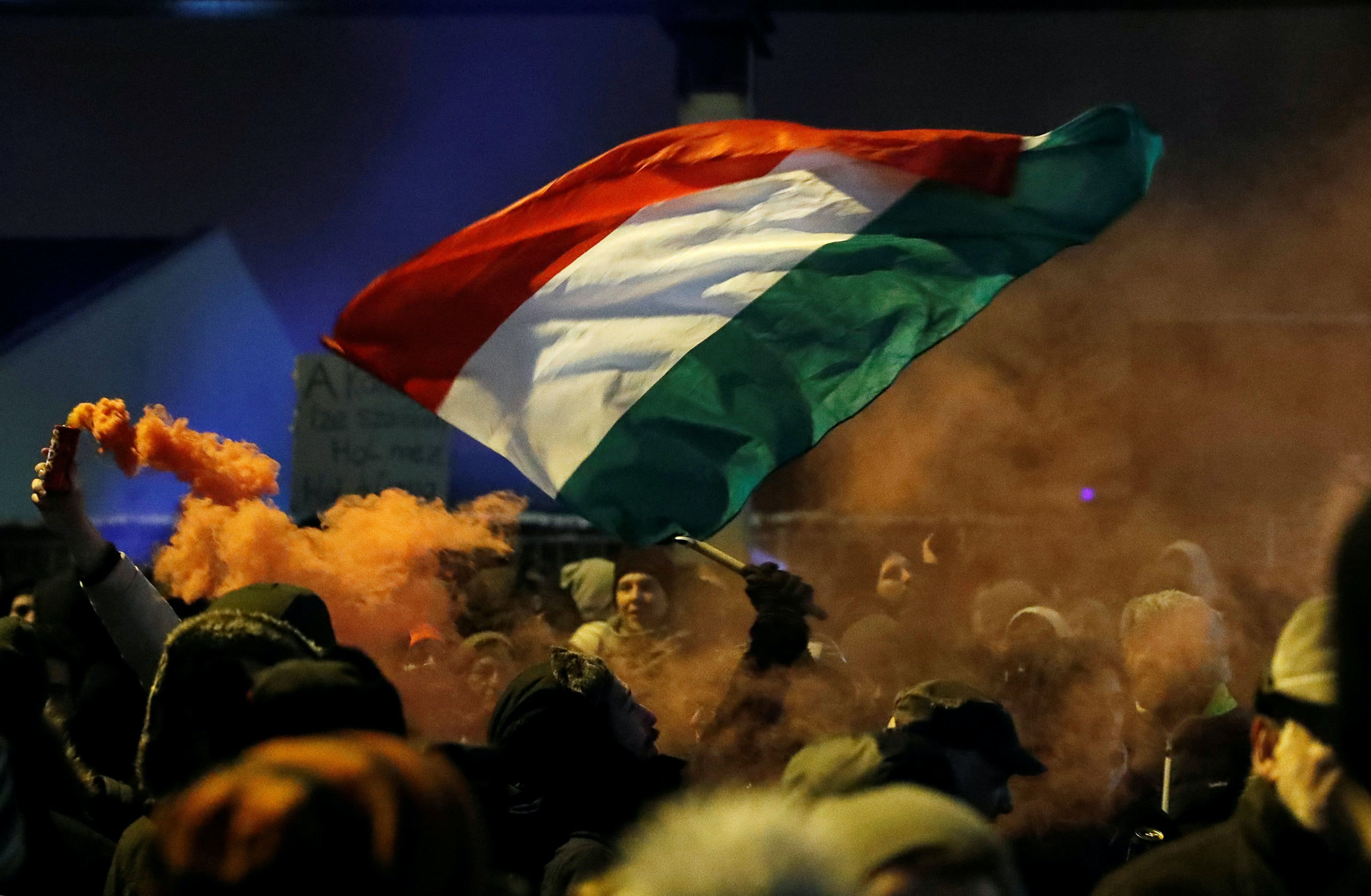 """Hungarian national flag and smoke from flares are pictured during a protest against a proposed new labor law, billed as the """"slave law"""", outside the headquarters of the Hungarian state television in Budapest, Hungary, December 17, 2018. REUTERS/Bernadett Szabo"""