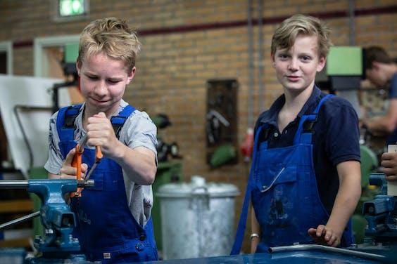 Jongeren van de techniekhavo krijgen tien uur in de week techniek. Hier zijn ze aan het werk met een bankschroef.