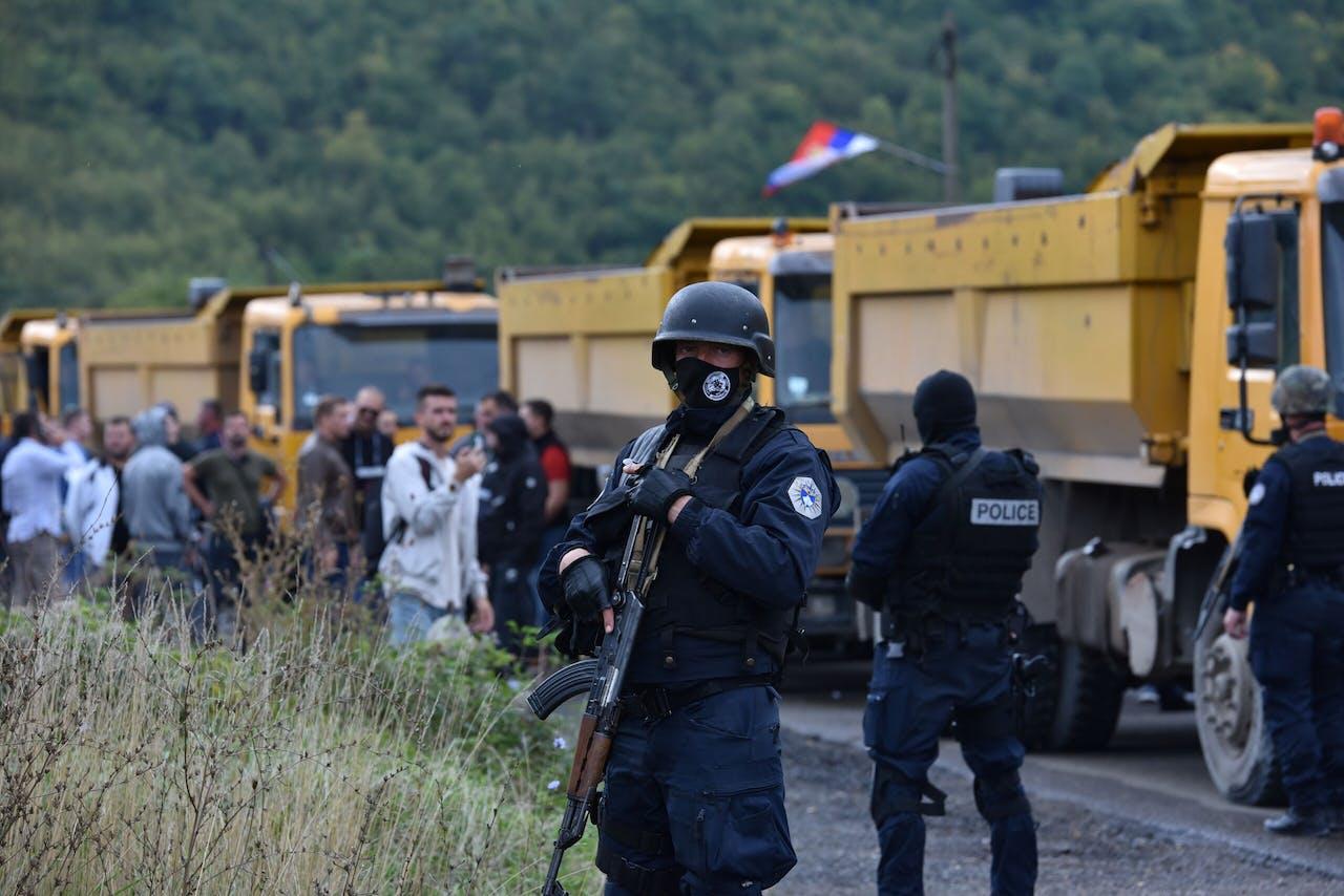Kosovaarse oproerpolitie houdt een oogje in het zeil bij een Servisch protest.