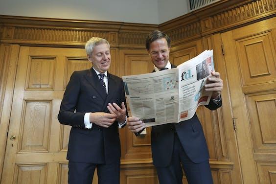 Premier Mark Rutte neemt het vernieuwde FD in ontvangst in het torentje, uit handen van hoofdredacteur Jan Bonjer.