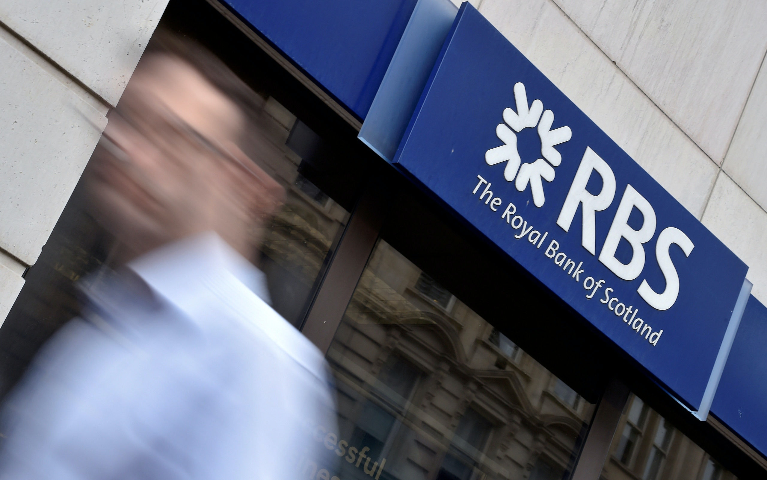FILE PHOTO: A man walks past a branch of The Royal Bank of Scotland (RBS) in central London, Britain August 27, 2014. REUTERS/Toby Melville/File Photo